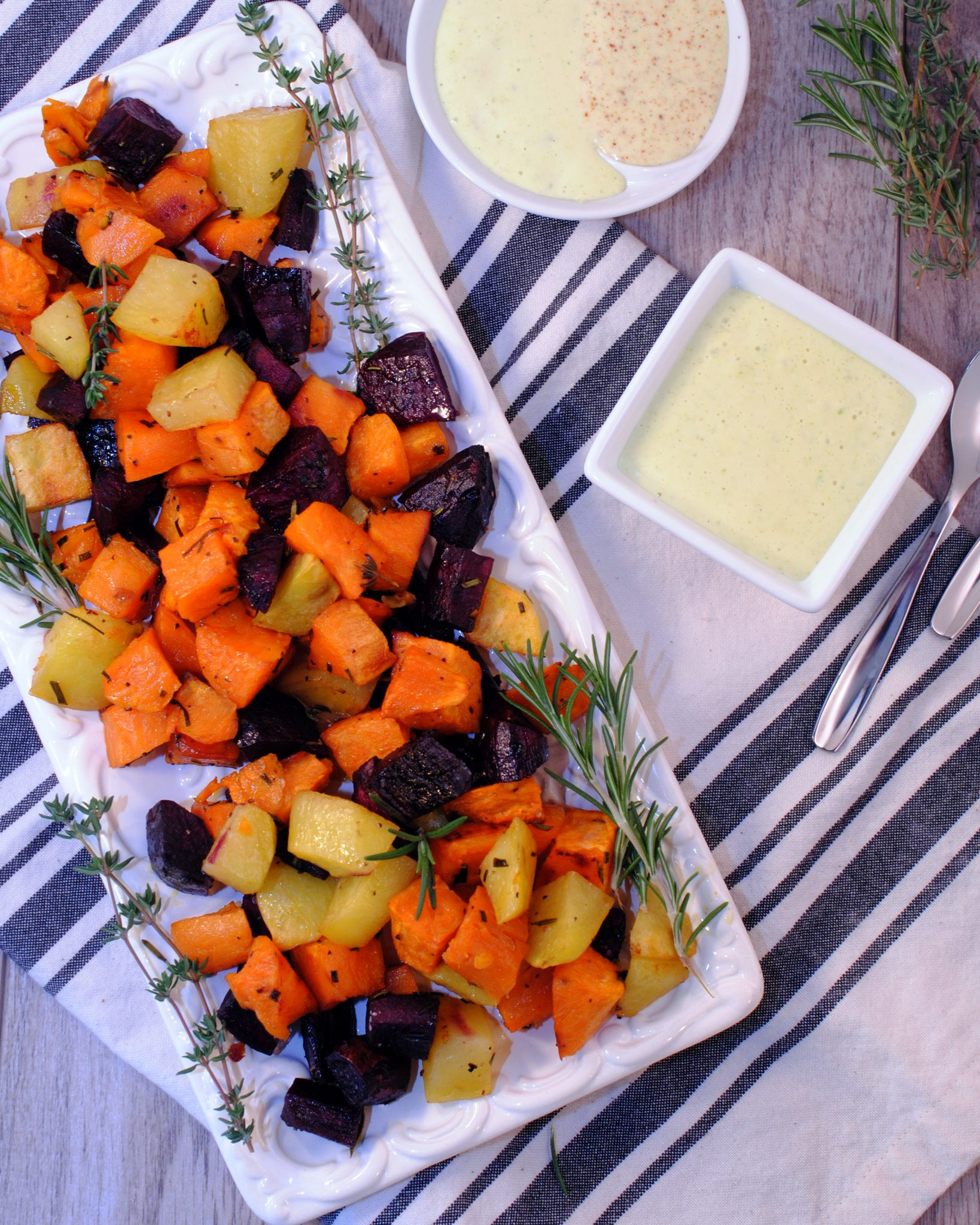 A savory roasted sweet potato flavored with fresh herbs of chives, rosemary, and thyme served with a rosemary garlic aioli sauce