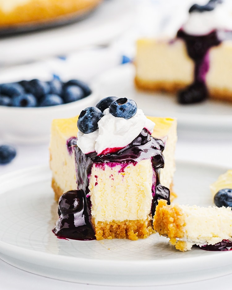 A slice of blueberry cheesecake with blueberry sauce and whipped cream on top with a fork bite taken out of the slice.