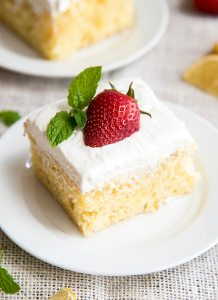 A slice of a yellow cake topped with a white frosting and a half a strawberry and a mint sprig on a small plate.