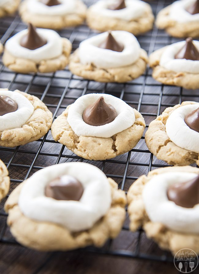 Hershey Kiss S'mores Cookies - These s'mores cookies start with a graham cracker filled cookie base, topped with a gooey marshmallow, and a chocolate kiss - for your favorite s'mores flavors in a delicious and cute cookie