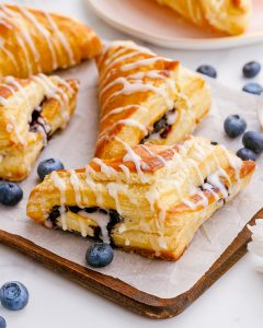 A few blueberry turnovers arranged on a piece of parchment on a wooden tray, with other blueberries scattered around them.