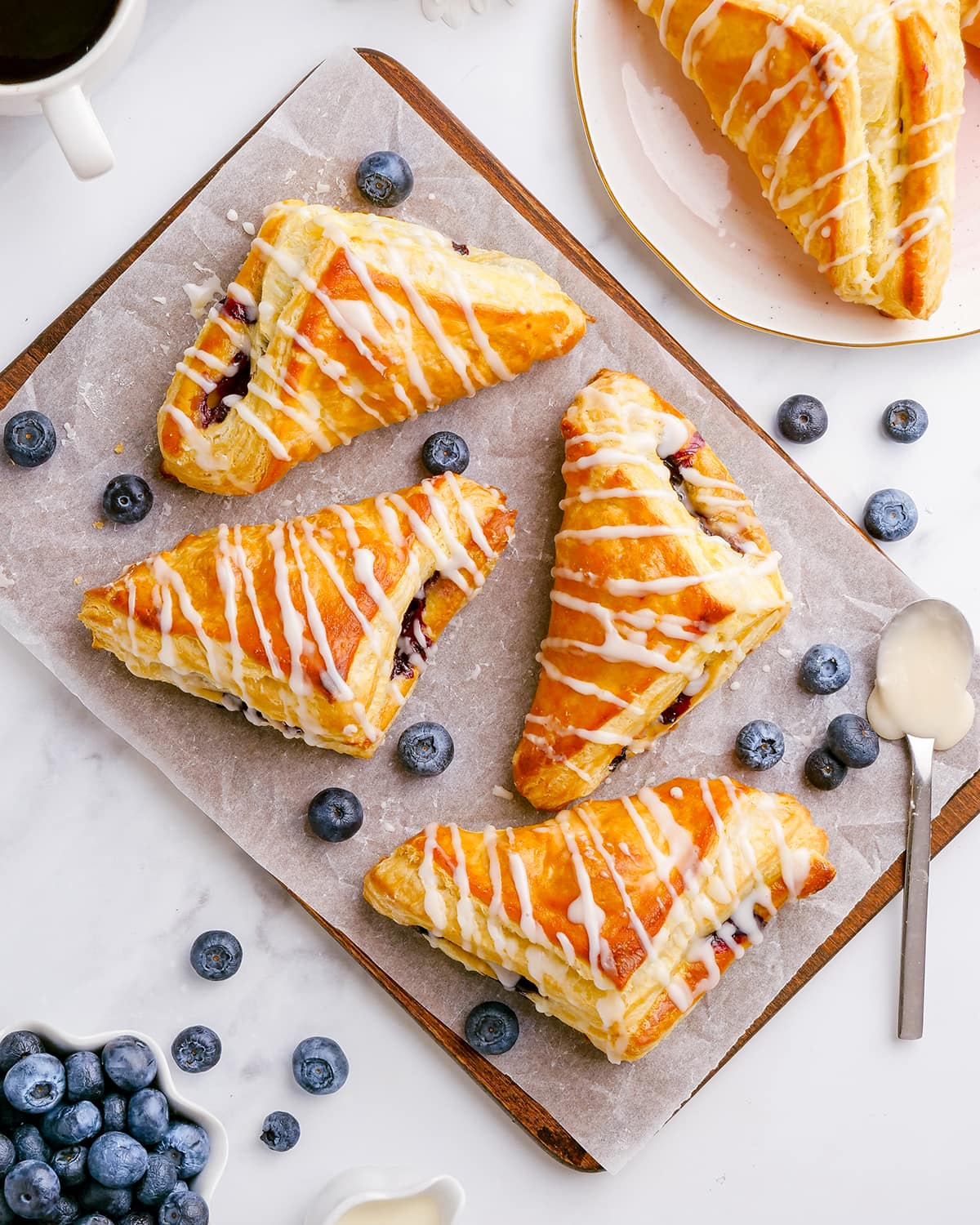 Four blueberry turnovers on a wooden tray, each drizzled with a powdered sugar glaze over the top.