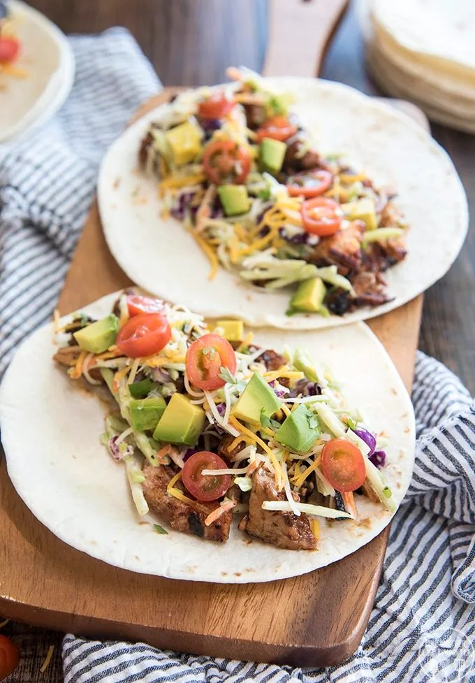BBQ Pork Tacos - These BBQ Pork Tacos are topped with a delicious creamy broccoli slaw, tomatoes, shredded cheese and your favorite taco toppings! It's like a pulled pork sandwich wrapped up in a delicious tortilla!