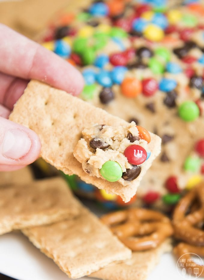 A chocolate chip peanut butter cookie dough dip covered in m&ms that is perfect for a crowd!