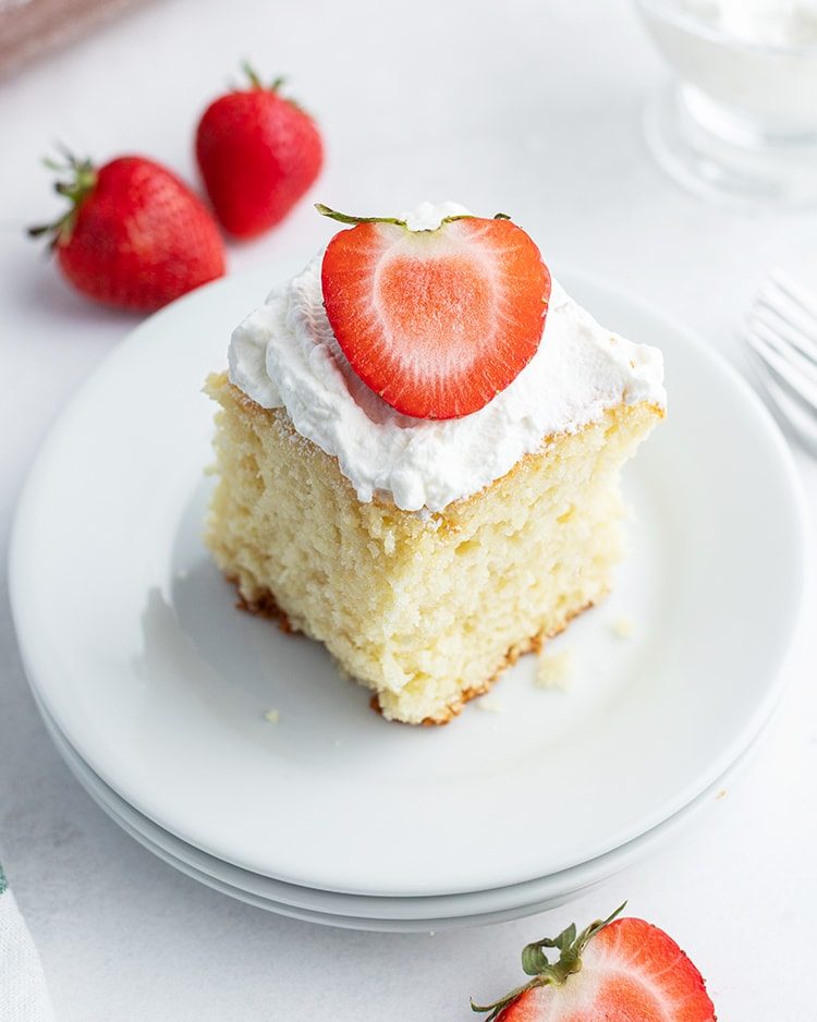 Strawberry yogurt cake topped with whipped cream and a strawberry.