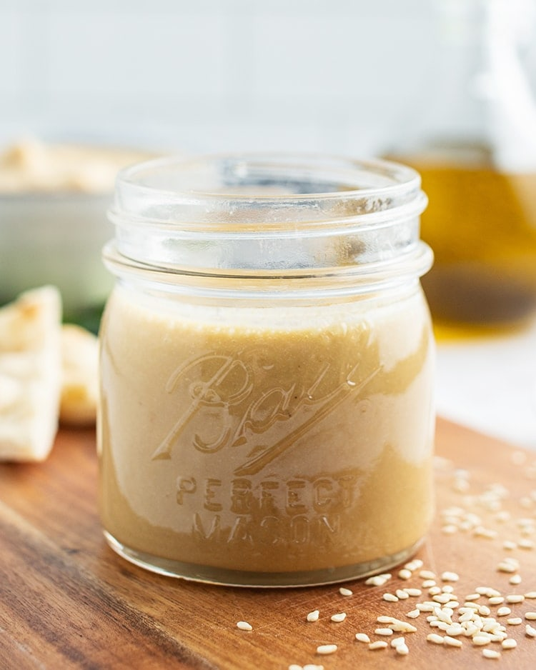 A close up of jar of tahini with a bowl of hummus, and a bottle of oil behind it.