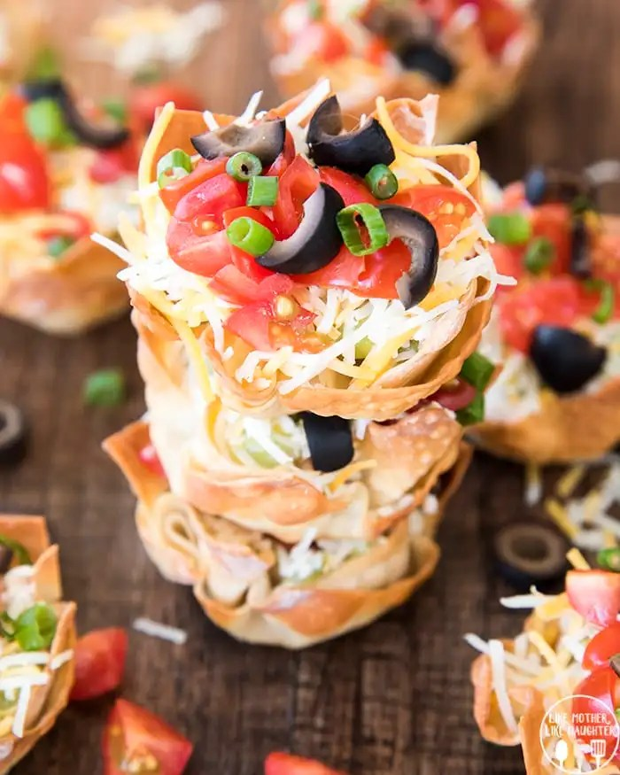 7 layer dip cups are individual wonton cups full of every layer of seven layer dip, perfect for a bite size, delicious, snack or appetizer, and great for a party!