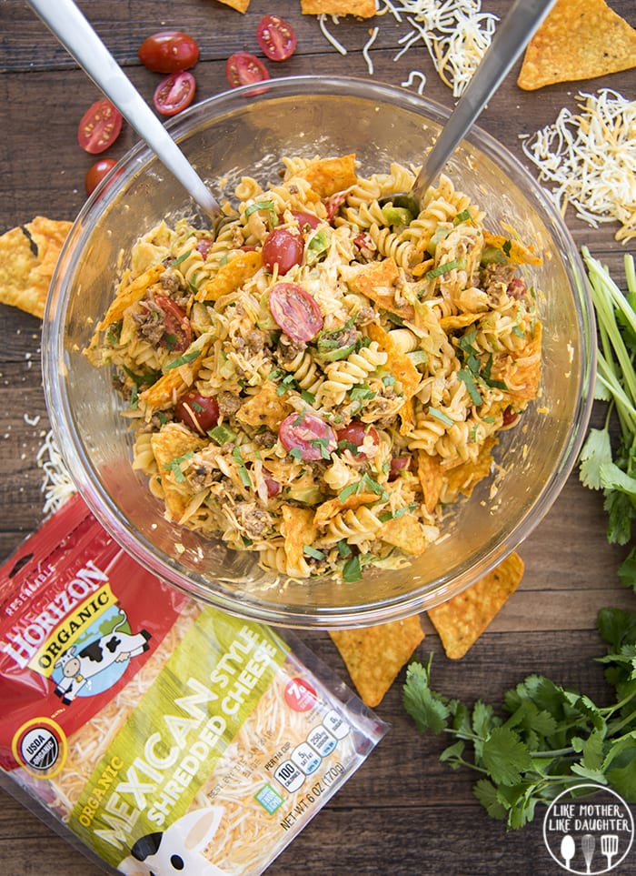 An overhead shot of a glass bowl full of a taco pasta salad, with rotini pasta, Doritos, tomatoes, ground beef, and topped with cilantro. Nest to it is some cilantro, nacho cheese chips, shredded cheese, and a package of cheese.
