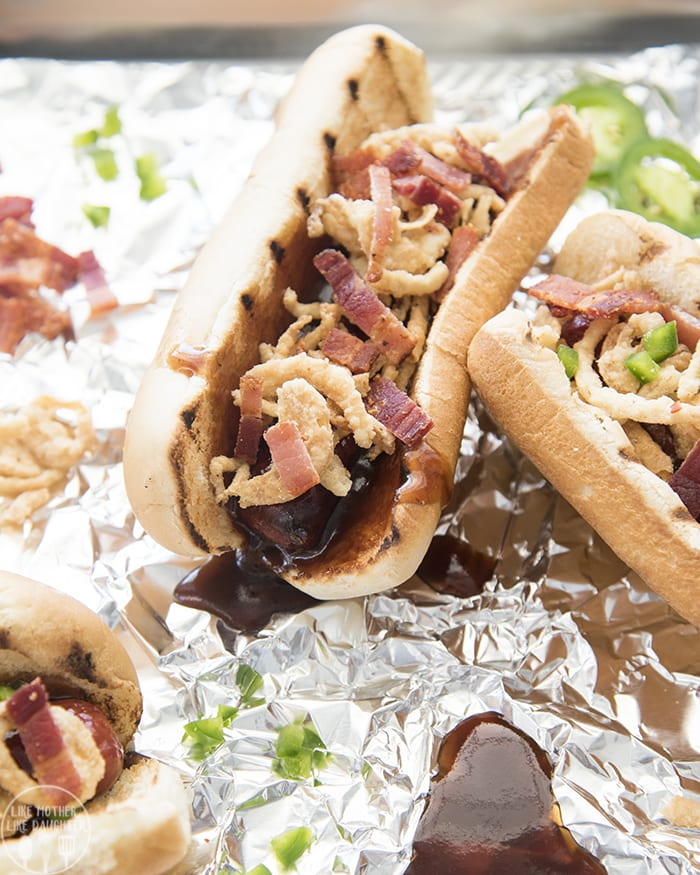 These BBQ Brats are topped with tangy BBQ sauce, crispy onion straws, salty bacon, and spicy jalapenos for a delicious twist that is perfect to eat all summer long!