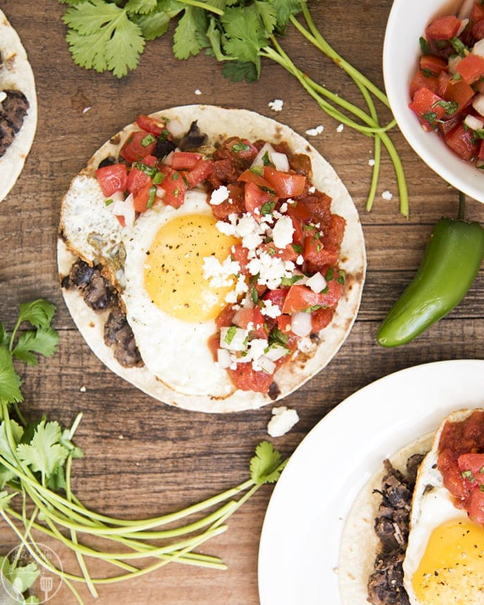 Huevos Rancheros are a delicious savory Mexican breakfast or brunch option! They start with homemade refried black beans on top of a corn tortilla topped with a fried egg, covered in warm salsa!
