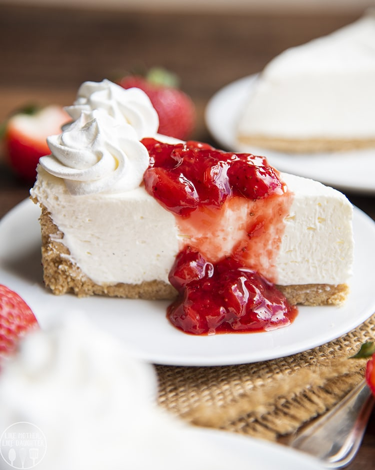 A slice of no bake cheesecake on a plate, with a thick graham cracker crust on the bottom and up the side, topped with two swirls of whipped cream, and fresh strawberry sauce.
