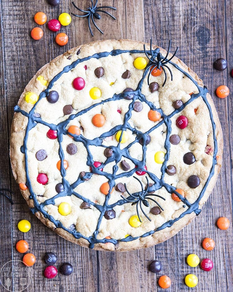 A giant chocolate chip cookie decorated like a spider web