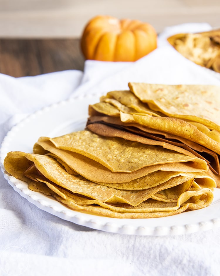 Pumpkin Crepes stacked on a plate and ready to be filled with your favorite crepe fillings