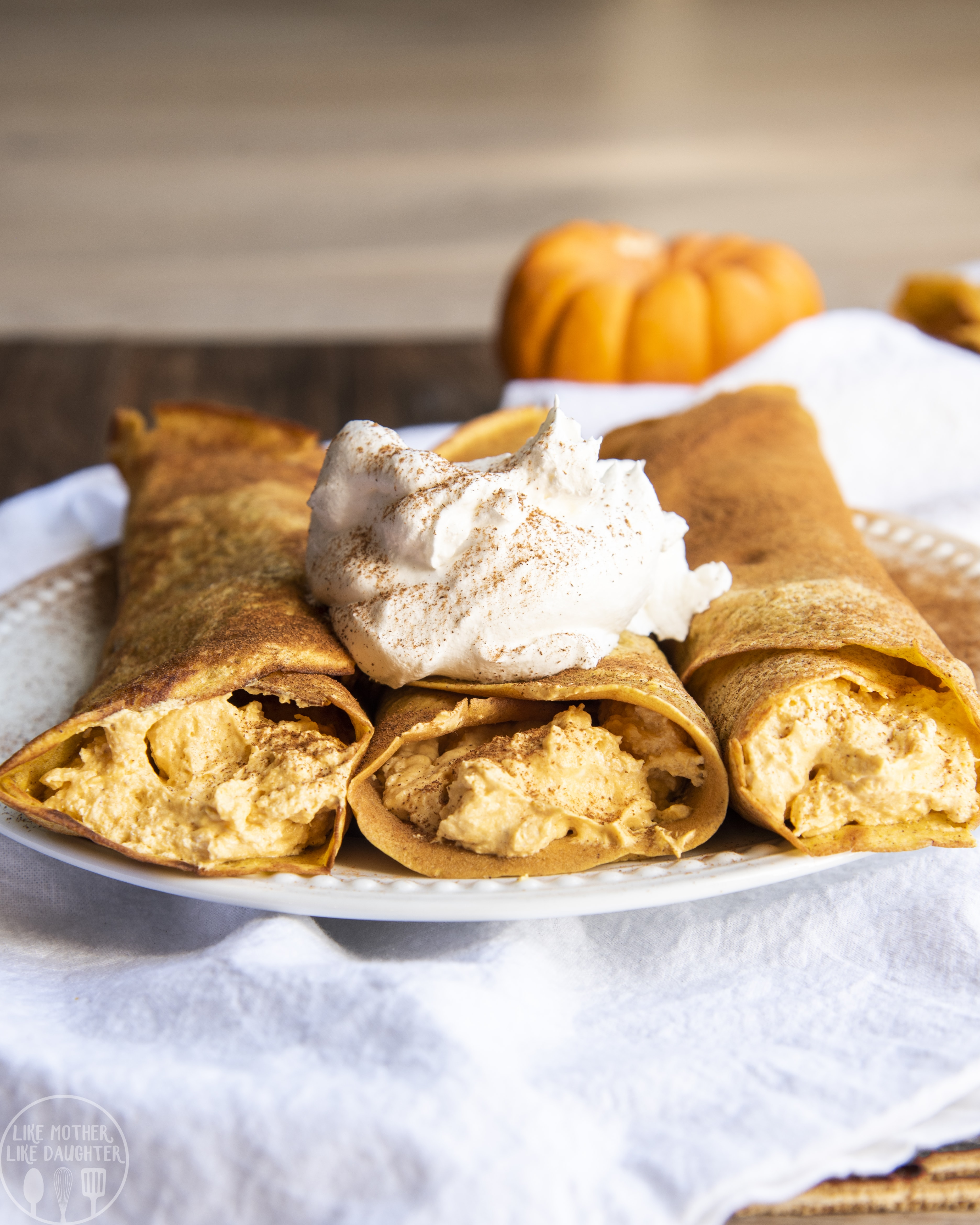 Pumpkin crepes with pumpkin cheesecake filling and topped with whipped cream