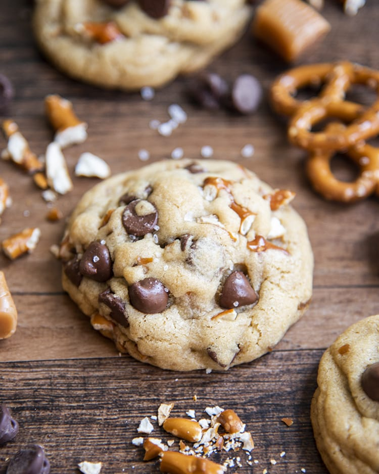 A salted caramel pretzel chocolate chip cookie on a brown backdrop