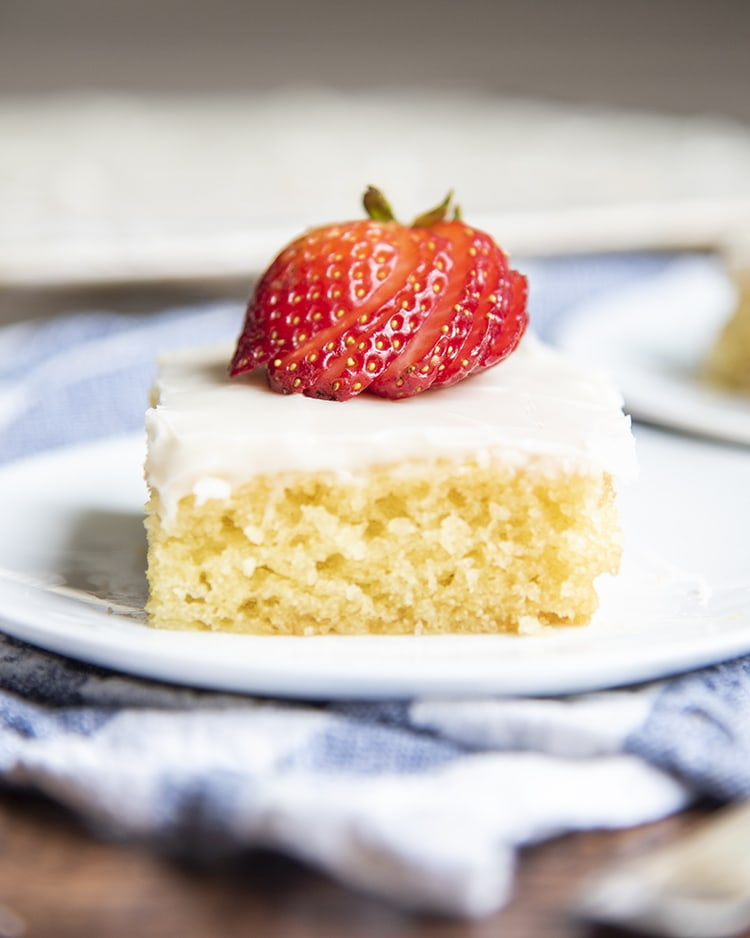 A slice of white texas sheet cake on a plate with strawberries on top.