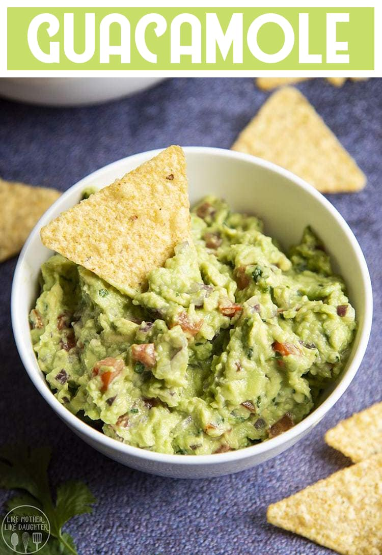 Homemade guacamole in a bowl with tomatoes, red onion, and chips in it with text overlay for pinterest