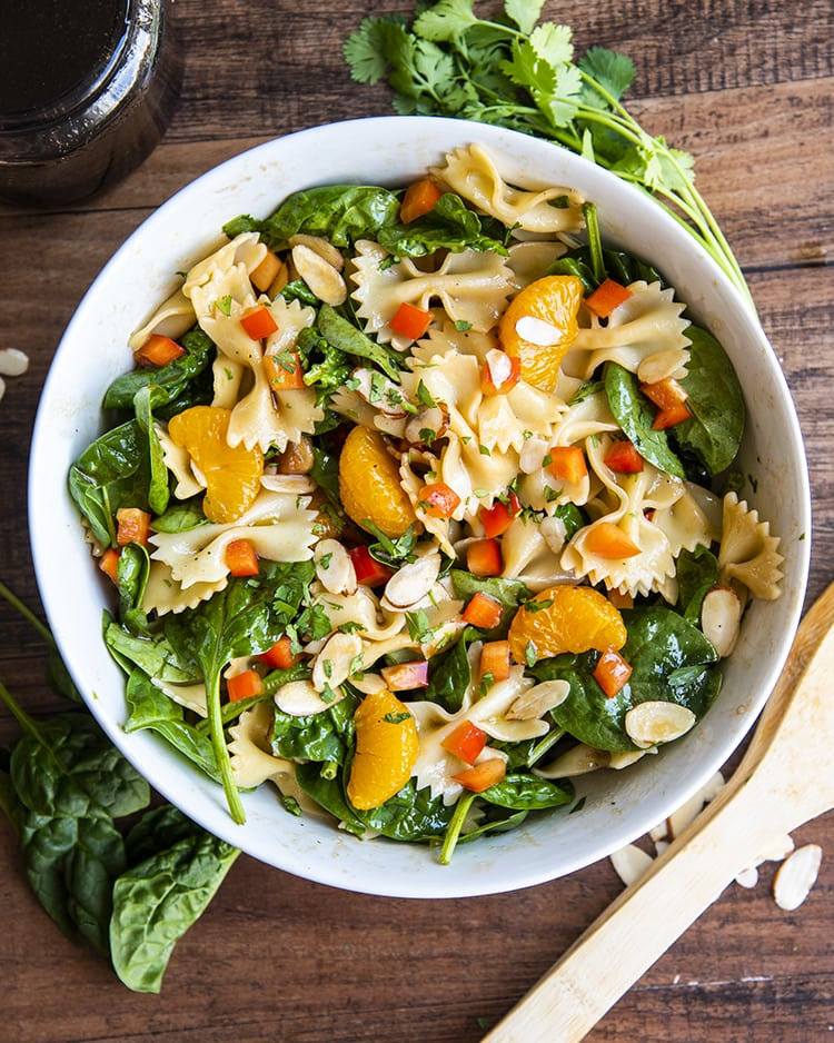 An overhead shot of a spinach pasta salad with bow tie noodles, mandarin oranges, spinach, cilantro, and bell peppers in a white bowl