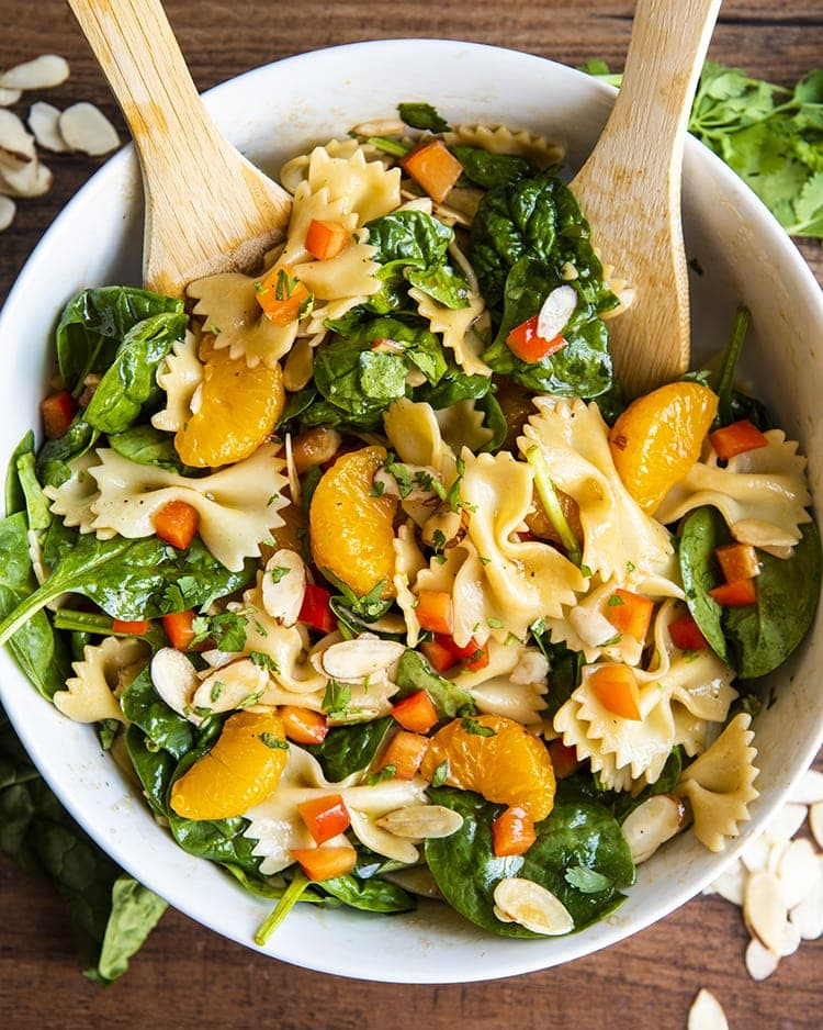 Asian pasta salad with spinach, mandarin oranges, red peppers, and sliced almonds tossed in a bowl with wooden spoons
