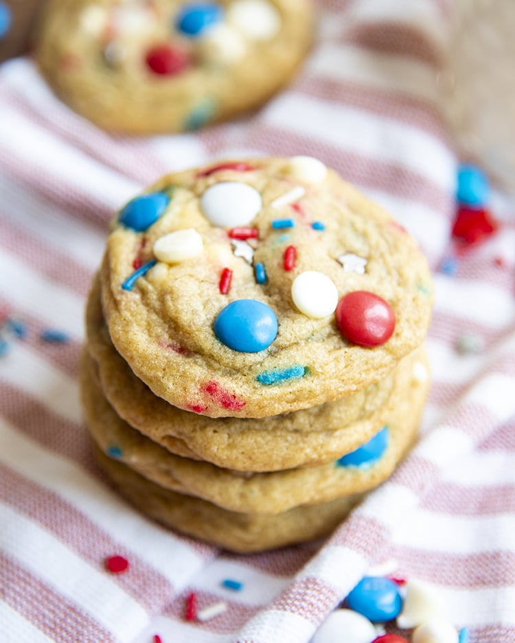 A stack of cookies filled with white chocolate chips, red, white and blue m&ms and sprinkles