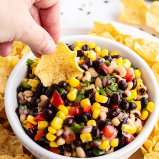 Texas caviar with a tortilla chip dipping into the bowl. The dip is full of black beans, black eyed peas, corn, bell pepper, and cilantro.
