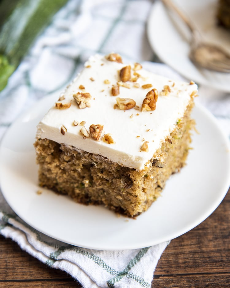 Zucchini cake with cream cheese frosting and pecans.