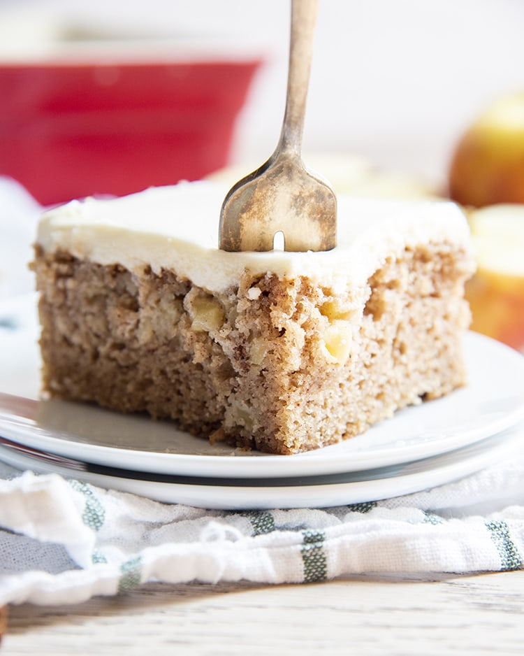 A slice of apple cake on a plate with a fork in it.