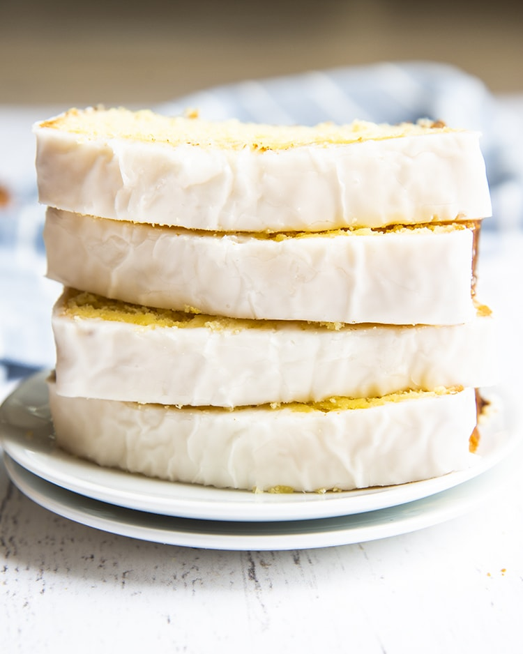 Slices of iced lemon loaf stacked on top of each other on a plate.