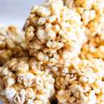 A stack of caramel popcorn balls in a white bowl.