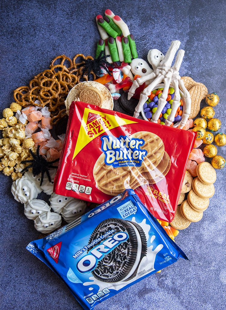 A Halloween treat charcuterie board shaped like a puumpkin topped with a package of NutterButters and a package of Oreos