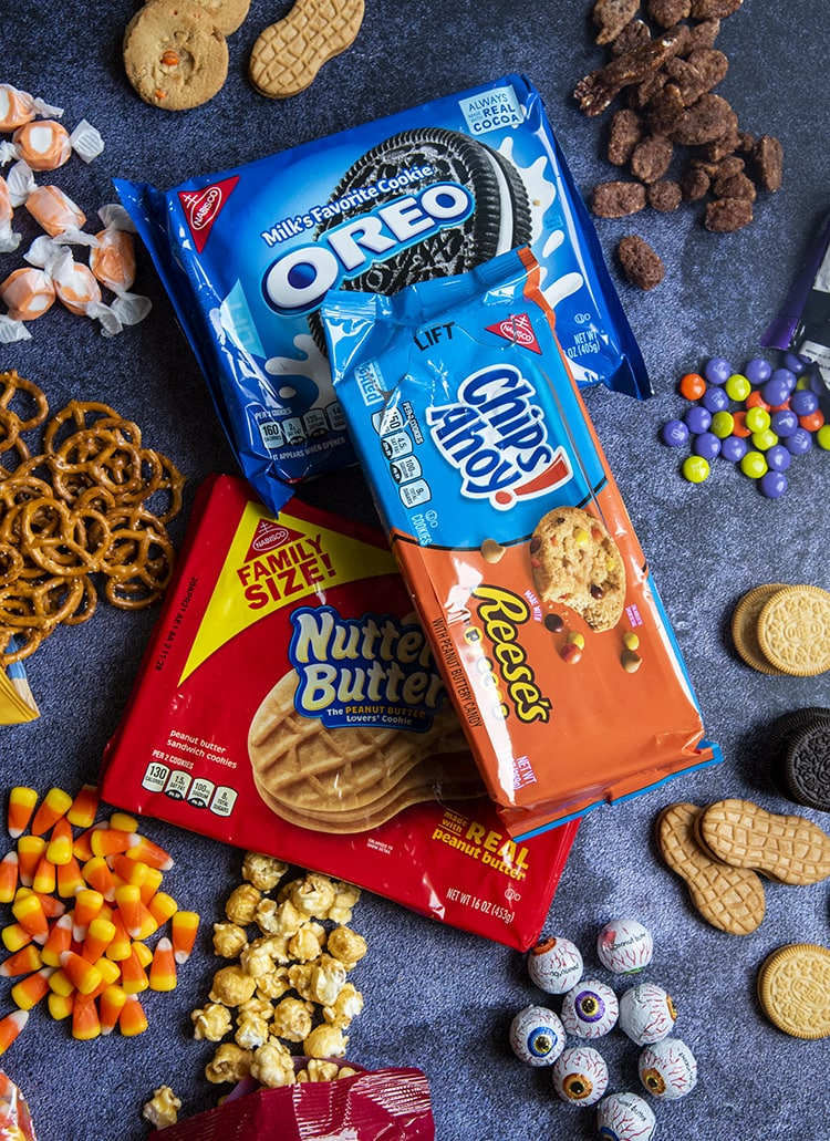 A package or Oreos and a package of Nutter Butters, and Reeses Pieces Chips Ahoy Cookies surrounded by pecans, m&ms, pretzels, caramel popcorn, candy eye balls, and taffy.