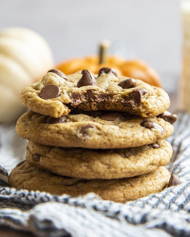 A stack of soft and chewy pumpkin chocolate chip cookies. The top cookie has a bite taken out of it.