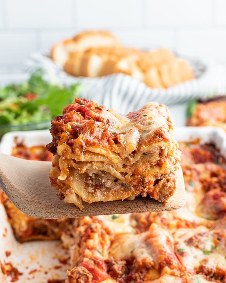 A piece of lasagna on a spatula being lifted out of the pan.