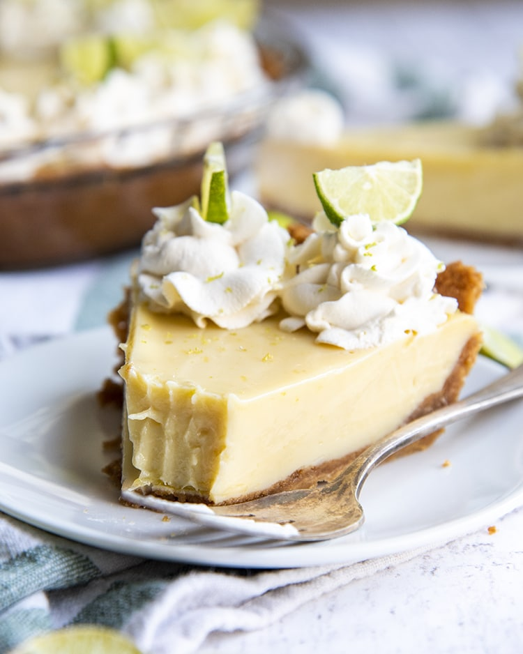 A slice of key lime pie with a bite taken out of it, opped with whipped cream rosettes and small lime slices, all served on a white plate.