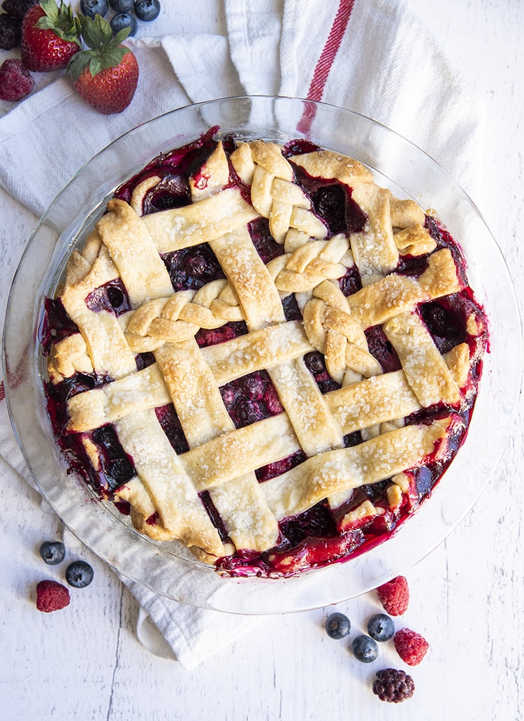 A berry pie with a lattice top, with a couple braided pieces of pie crust on top too.