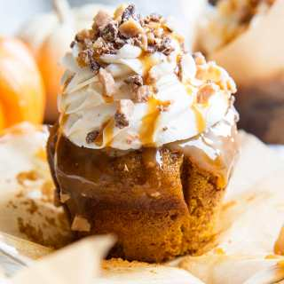 A pumpkin better than sex cupcake with caramel dripping down the sides, topped with cream cheese frosting, and a a caramel drizzle, and toffee bits.