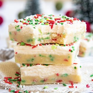 A stack of sugar cookie bars filled with red and green jimmie sprinkles, and topped with a white frosting, and more sprinkles. The top bar has a bite taken out of it.