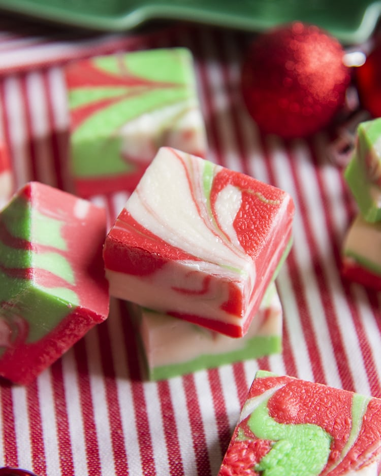 Christmas swirled fudge, on a red and white cloth. The fudge has red, white and green colors swirled throughout.