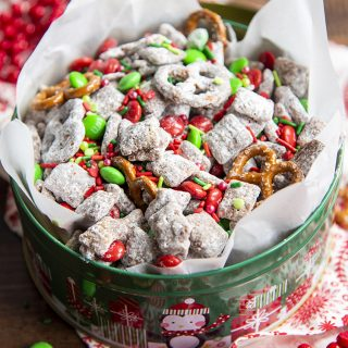 A christmas tin full of Reindeer chow which is muddy buddies with red and green m&ms, and mini pretzels.