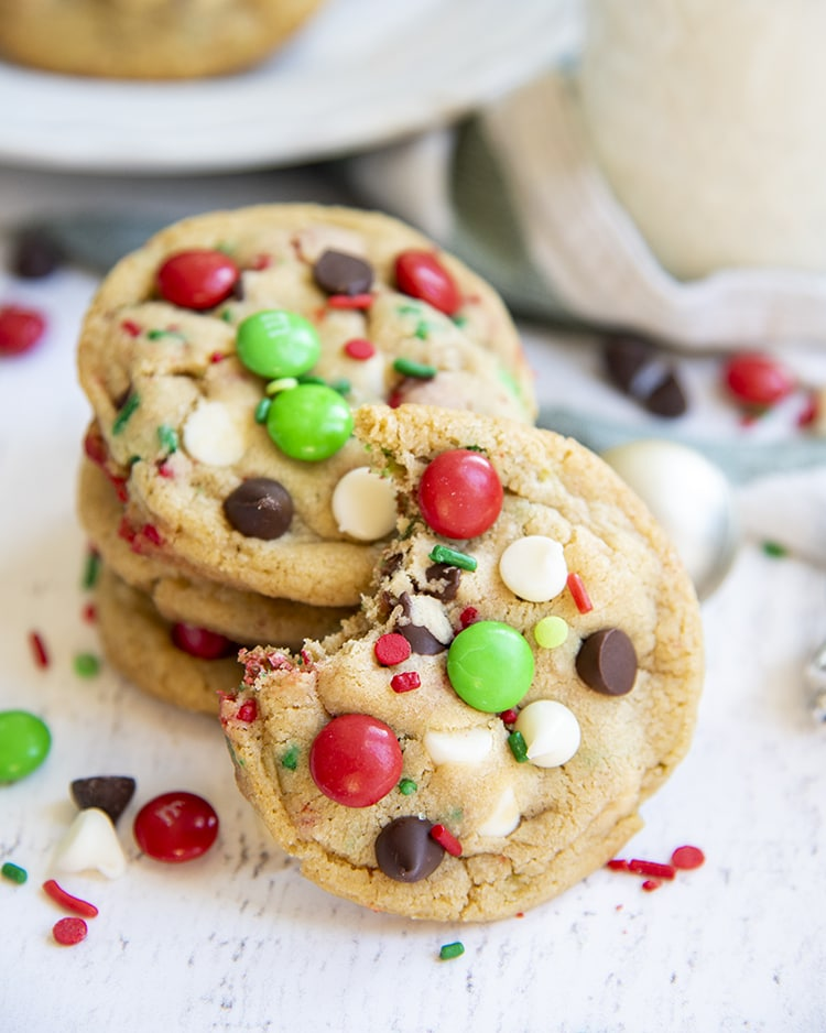 Christmas cookies stacked in a pile with one cookie in front with a bite taken out of it.