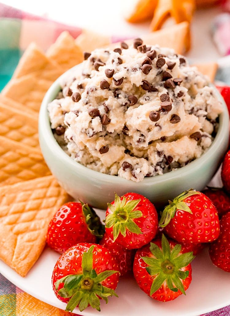 A small bowl of cannoli dip sprinkled with mini chocolate chips. The bowl is a on a plate with crepe cookies, and strawberries.