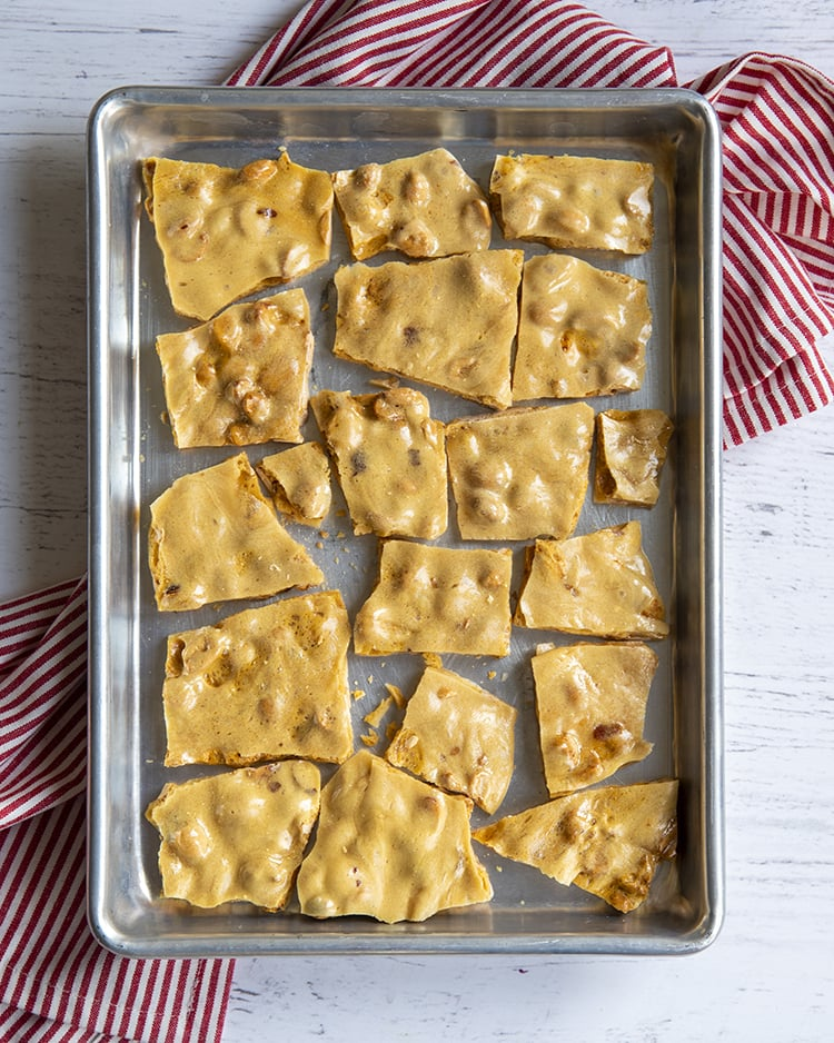 A cookie sheet covered in broken pieces of peanut brittle.