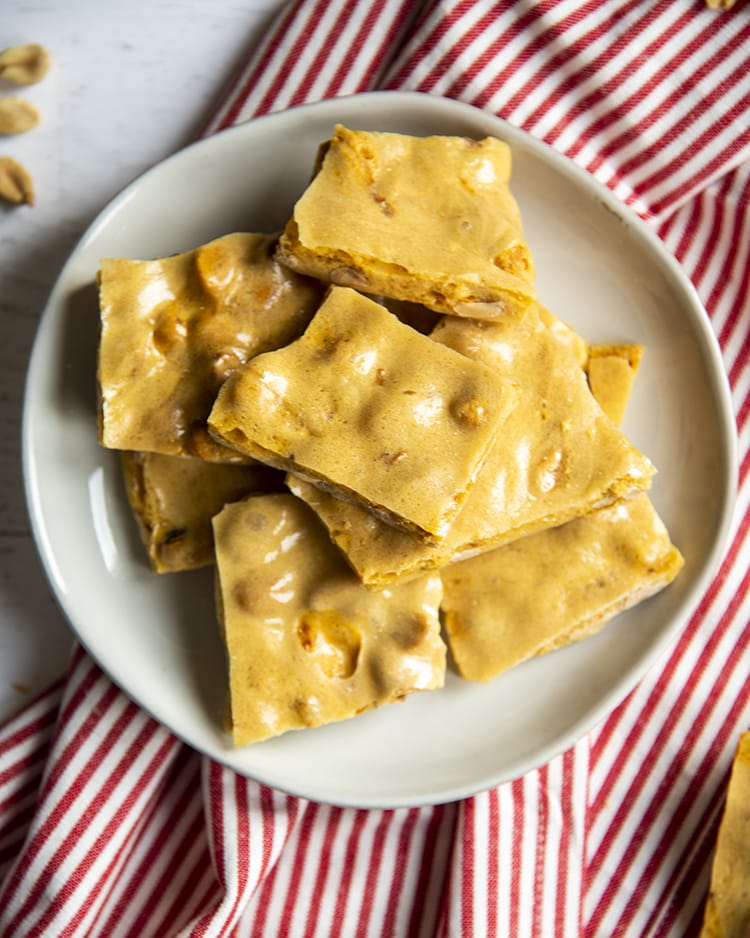 A white plate that is loaded with a pile of yellowish brown colored peanut brittle pieces.