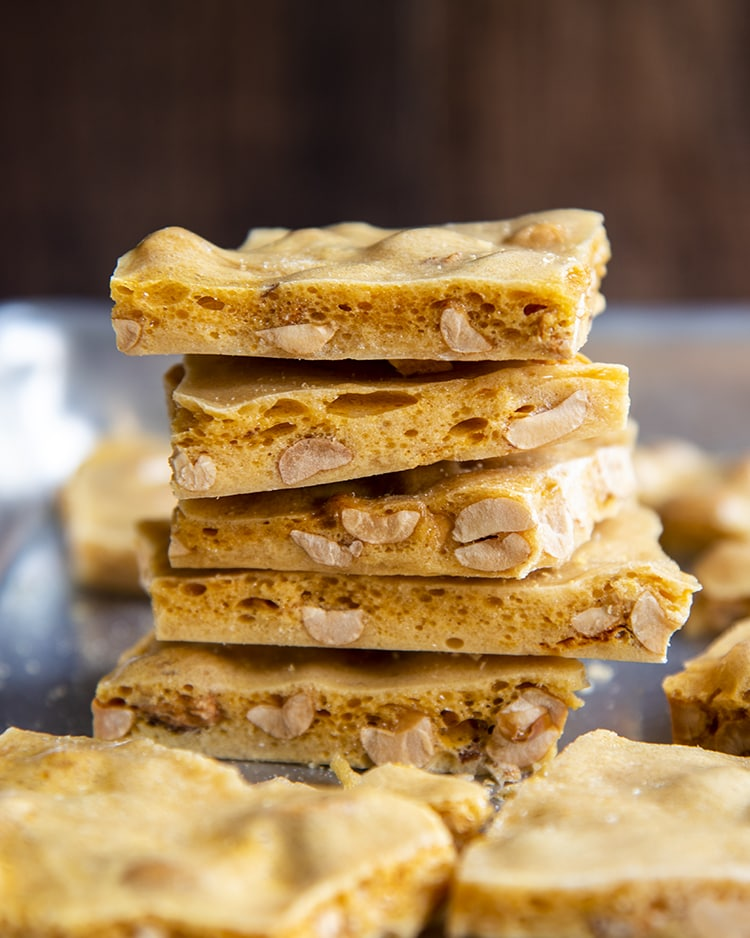 A stack of 5 pieces of peanut brittle showing the light airy layers, with bubbles in the brittle, and peanuts inside.