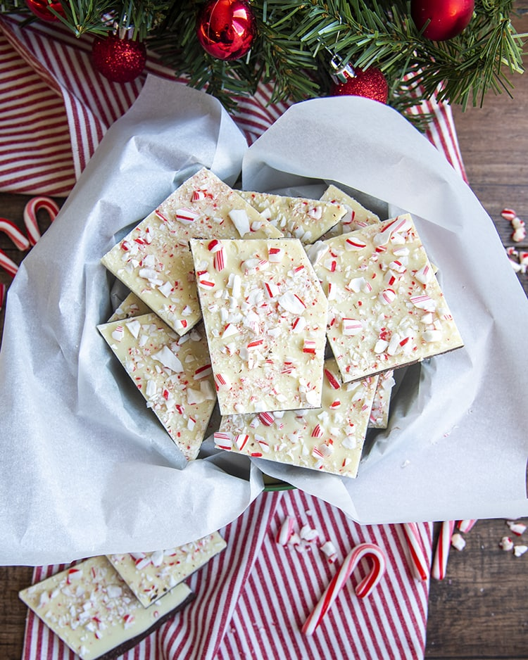 A pile of peppermint bark in a Christmas tin with parchment paper.