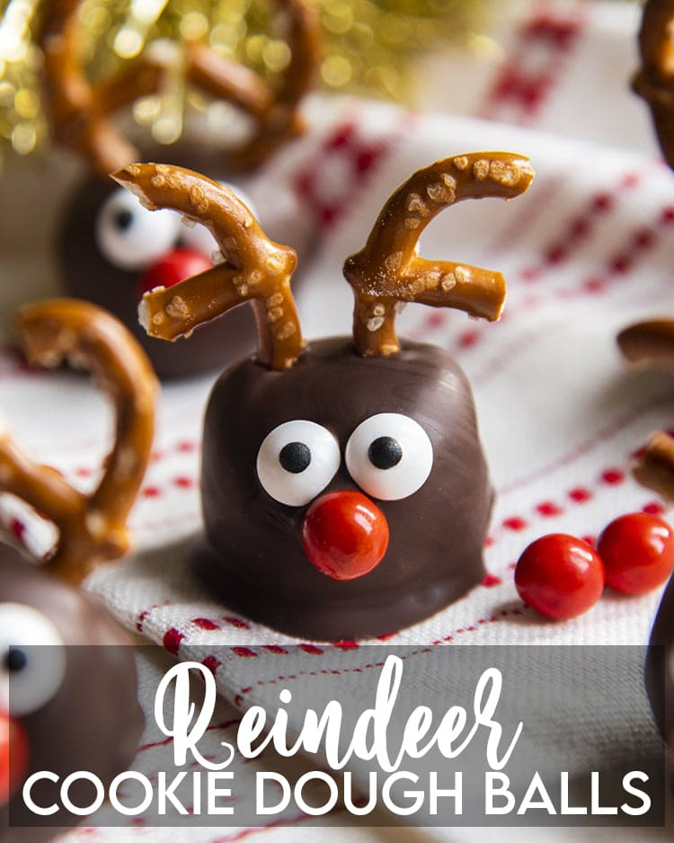 A cookie dough ball covered in chocolate, and decorated with pretzels, candy eyes and a red nose to look like a reindeer. On a white and red cloth with a text overlay for pinterest.