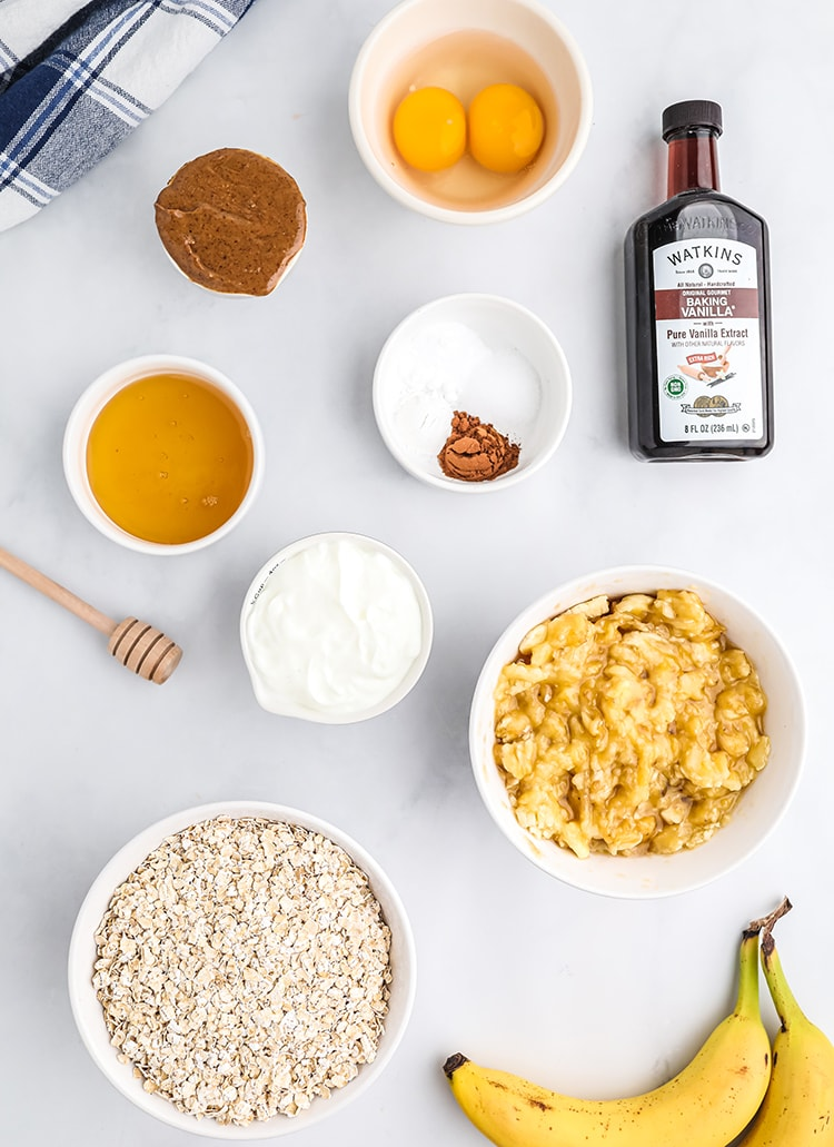 The ingredients needed to make banana cinnamon oatmeal muffins, laid out in bowls. There are eggs, almond butter, honey, oats, greek yogurt, mashed bananas, a bottle of vanilla extract, and a small bowl with baking powder, baking soda, and cinnamon.