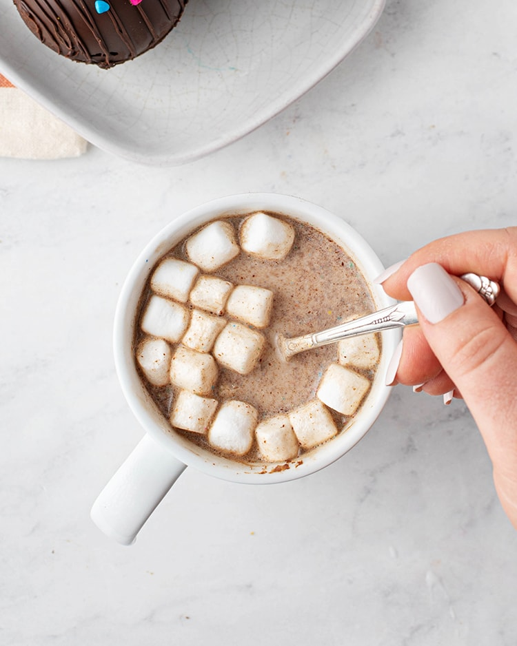 A white mug filled with hot cocoa, and mini marshmallows. A hand is holding a spoon in the mug.
