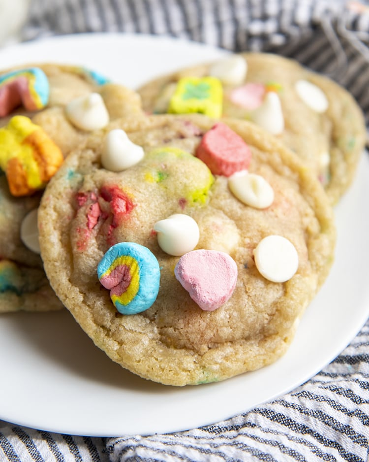 A close up of a cookie on a white plate, with two more cookies behind, the cookie is filled with white chocolate chips and lucky charms marshmallows.