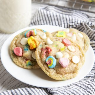 The lucky charms cookies on a small white plate with a glass of milk behind. On top of the cookies there are lucky charms marshmallows, and white chocolate chips.